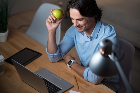 enjoyable: Enjoyable work time. Happy handsome young man using laptop and holding an apple while sitting at the table.