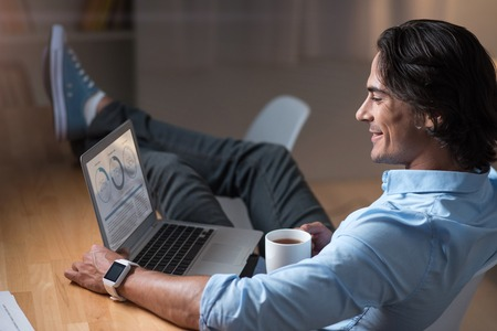 devise: Relaxed working time . Handsome smiling young man sitting at the table and using laptop while drinking tea.