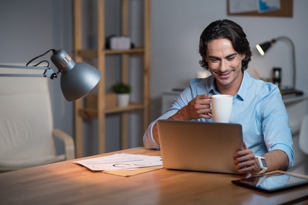 Work with inspiration. Handsome busy young man sitting at the table and drinking tea while using tablet. Stock Photo