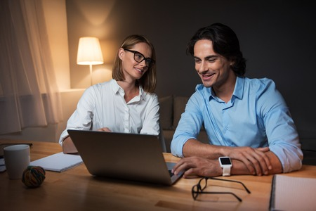 to be pleasant: Happy to be colleagues. Pleasant colleagues working on a project in an office and using laptop together Stock Photo