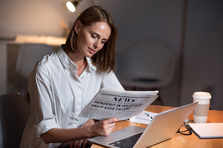 evening newspaper: What is news. Positive beautiful woman sitting at the table and holding newspaper while reading it