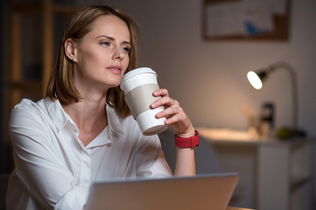 Mull over it. Pleasant beautiful concentrated woman sitting at the table and thinking while drinking coffee Stock Photo