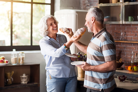 aging woman: Happy aging. Nice classy man and woman feeding each other with cruassans and laughing Stock Photo