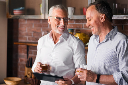 collegue: Old experienced manager showing his collegue new material on tablet while having a drink in the kitchen Stock Photo
