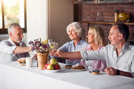 grownup: Happy toasting. Grown-up children visiting their old parents Stock Photo