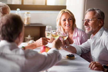 aging american: Celebrating. Smiley group of white people cheering with white wine while having a party