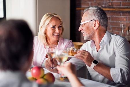Charmante glimlach. Blonde milf die een bejaarde in glazen bekijkt, terwijl hij haar een croissant aanbiedt Stockfoto