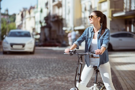 actively: Live actively. Cheerful young beautiful woman looking aside and smiling while riding a bicycle