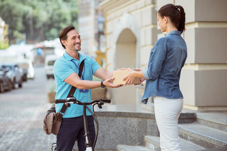 Working for your comfort. Cheerful professional courier smiling and holding a parcel while delivering it to the client Stock Photo