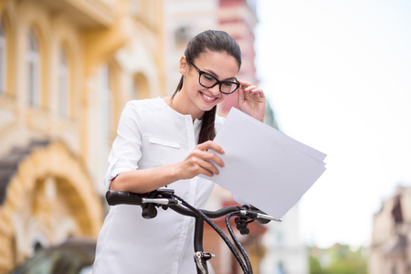 gladness: Live with positivity. Joyful delighted beautiful woman holding papers and standing near bicycle while expressing gladness Stock Photo