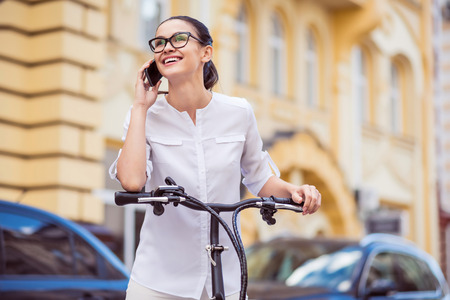 Call me back soon. Positive charming delighted woman standing near bicycle and talking on cell phone while expressing joy Stock Photo