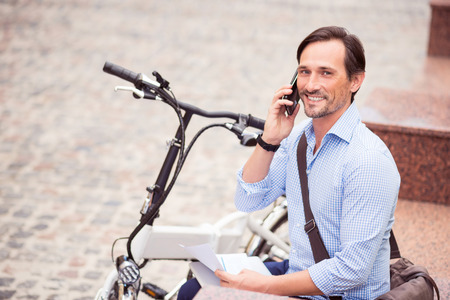 potěšen: Pleasant talk. Cheerful adult delighted man smiling and talking on cell phone while sitting in the street Reklamní fotografie