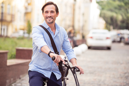 activate: Activate your life. Cheerful delighted adult man smiling and riding a bike while resting outside Stock Photo