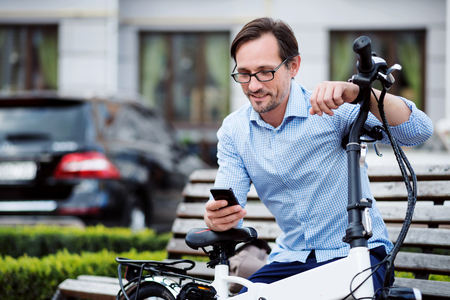 bespectacled: Virtual communication. Handsome bespectacled man putting his hands on bike and using laptop while sitting on the bench.