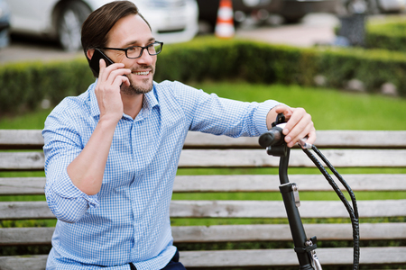bespectacled: Joyful conversation. Handsome bespectacled man speaking on cellphone and smiling while sitting on the bench.