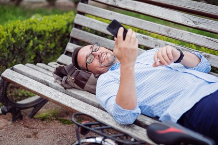 grizzle: Nice message. Grizzle joyful man using cellphone and smiling while lying on the bench. Stock Photo