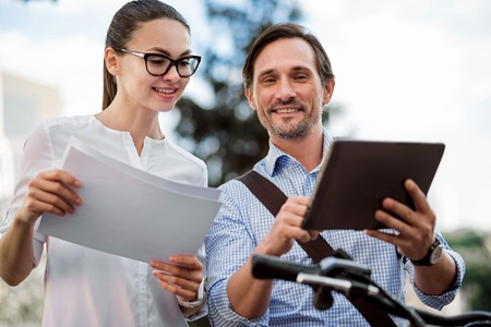 Prepare as you can. Successful young smiling colleagues going to work and preparing for it using the tablet Stock Photo