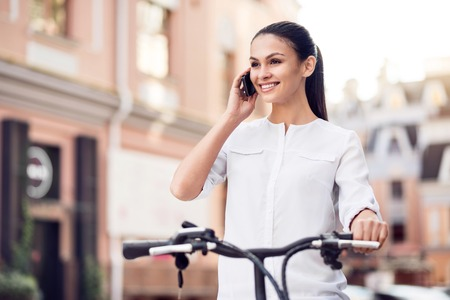 tempo: Quick tempo of life. Positive delighted beautiful woman talking on cell phone and riding a bicycle Stock Photo