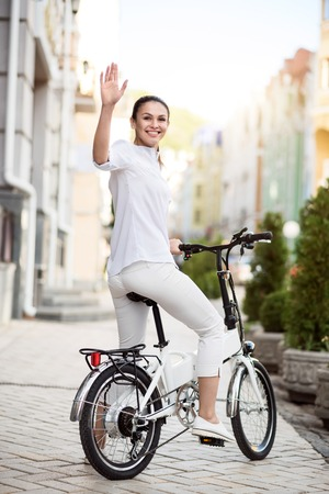 good bye: See you soon. Positive delighted woman smiling and riding a bike while saying good bye Stock Photo