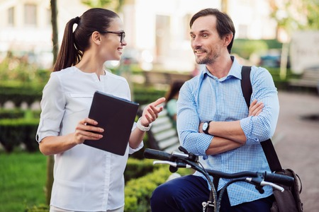 ambitious: You will not believe. Happy ambitious woman telling her young male colleague on a bicycle surprising news.