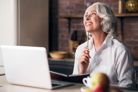 Happy morning. Good-looking grey woman enjoying her breakfast while thinking of writing a letter to her family Stockfoto