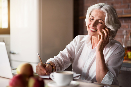 happieness: Smiley. Pleasant old lady communicating with her family and friends using telephone and laptop