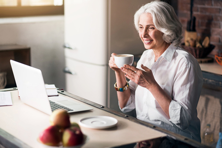 likeable: Pleasure of communication. Attractive old lady checking her e-mail at light spacious kitchen
