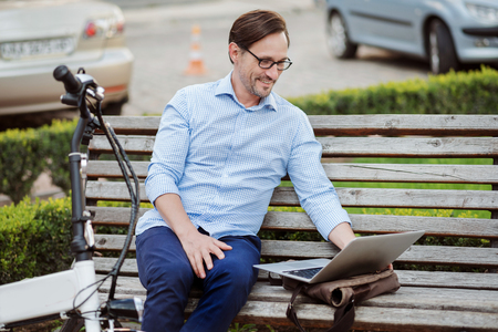 What a wonderful work. Glad handsome bespectacled man working on laptop and smiling while sitting on the bench.