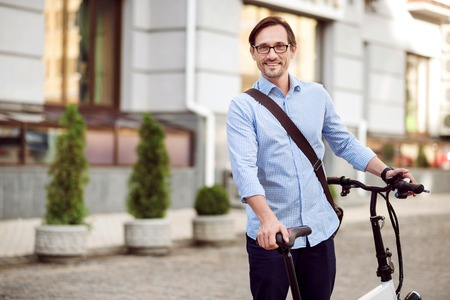 bespectacled: Happy ride. Handsome bespectacled man smiling and keeping bike while standing in the street.