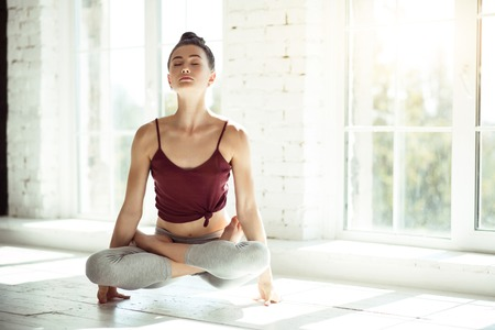 paz interior: Experimentar la paz interior. Hermosa chica agradable delgado que se sienta con las piernas cruzadas y tocar el piso solamente con sus manos mientras se practica el yoga
