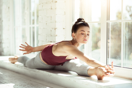 splits: Productive workout. Nice good looking brunette dancer doing the splits and bending her body while sitting near the window