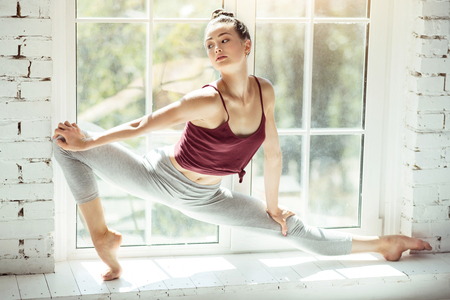 Stretching exercises. Serious good looking brunette dancer standing on a windowsill and doing her physical exercises while training Stock Photo