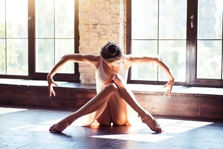 Bellezza nella plasticità. Professionale ballerina bruna attraente che attraversa le gambe e spostando le braccia mentre era seduto sul pavimento