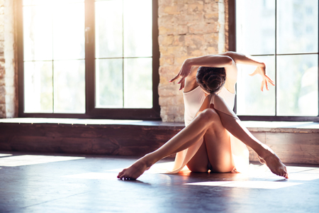 Aesthetic and beautiful. Pretty nice female dancer moving her arms and bending her head forward while sitting cross legged on the floor