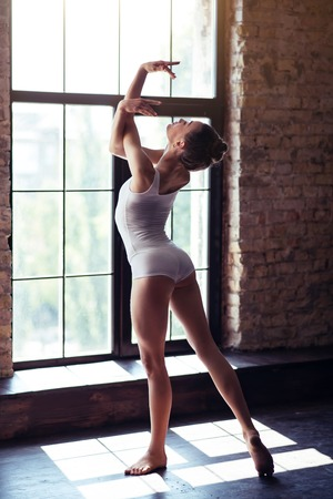 talented: Graceful posture. Talented skillful professional dancer standing near the window and holding her hands up while enjoying the sunbeams