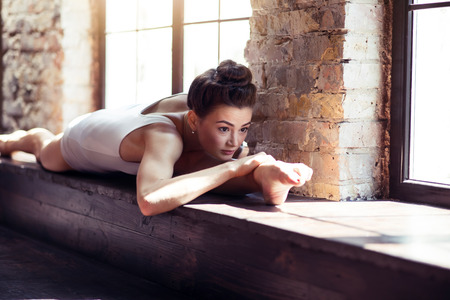 splits: Incredible flexibility. Good looking attractive talented woman sitting on a windowsill and concentrating on the exercise while doing the splits Stock Photo