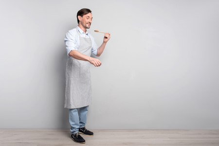 Yummy dish. Happy young working handsome man holding a spoon and tasting something good on a grey background