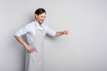 Good cook. Smiling joyful man salting the dish carefully while cooking standing on a grey background