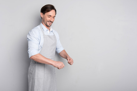 Nice work. Smiling young ambitious man gesturing like cooking and holding something while standing on a grey background Stock Photo