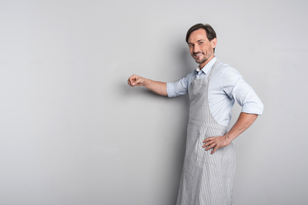 Good meal. Young handsome joyful man in an apron pretending like cooking standing on a grey background.