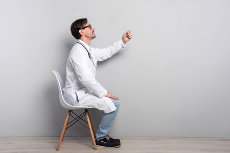 diagnosing: I will cure you. Young handsome talented doctor in smock gesturing like diagnosing his patient