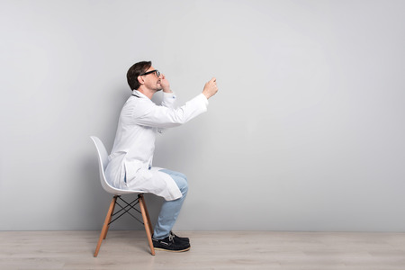 diagnosing: Be healthy. Concentrated young ambitious doctor sitting on a chair while diagnosing his patient with stethoscope on a grey background. Stock Photo