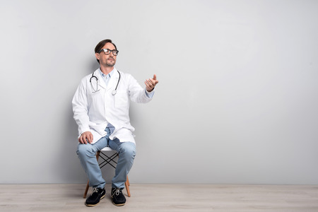 Lovely work. Concentrated handsome young doctor sitting on a chair on a grey background while thinking about his work and gesturing