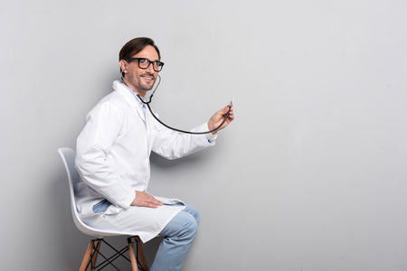 diagnosing: Ready to help. Joyful young handsome doctor using a stethoscope while sitting on a chair beyond grey background and diagnosing the patient Stock Photo
