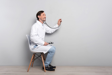 diagnosing: Here for you. Young happy ambitious doctor doing his work by using the stethoscope and diagnosing the patient Stock Photo