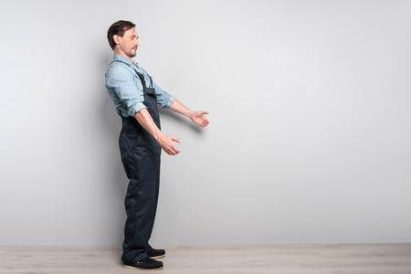 diligente: Mucho trabajo por hacer. leasant diligente hombre mayor de camiones y Holdign workign mientras que de pie aislado en fondo gris