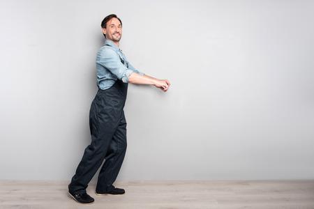 diligente: trabajador real. Agradable encantados hombre diligente camión Holdign y sonriendo mientras está de pie aislado en fondo gris Foto de archivo