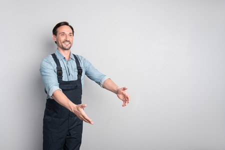 describe: Look here. Handsome cheerful pleasant man moving his hands and smiling while trying to describe something Stock Photo