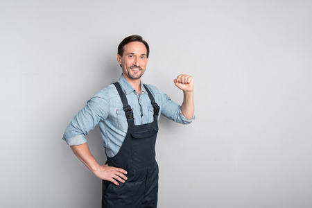 confidently: I can do everything. Good looking charismatic male worker clenching the fist and standing confidently while showing his strength