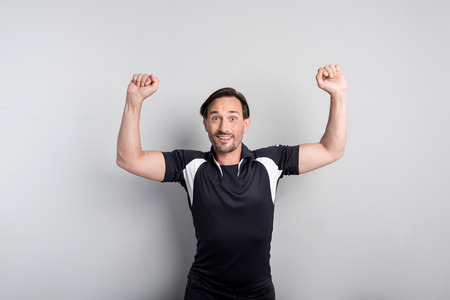 well built: Strong sportsman. Good looking well built slim man holding his hand up and smiling while showing his muscles